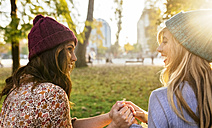 Two young women wearing wooly hats in a park in autumn - MGOF02603