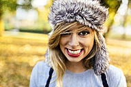 Portrait of smiling young woman wearing fur hat - MGOF02606