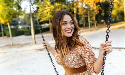 Smiling young woman on a swing - MGOF02609