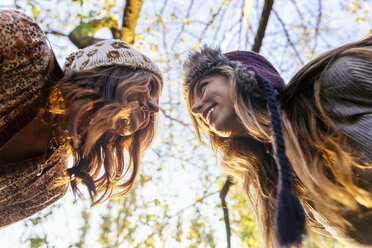 Two young women wearing wooly hats facing each other - MGOF02612