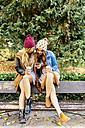 Two young women with smartphone in a park in autumn - MGOF02615