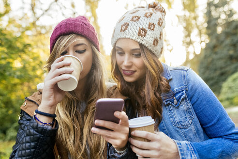 Two young women with smartphone in a park in autumn - MGOF02618