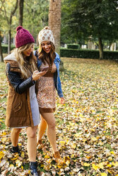 Two young women with smartphone walking in a park in autumn - MGOF02621