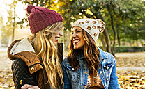 Two smiling young women wearing wooly hats in a park in autumn - MGOF02624