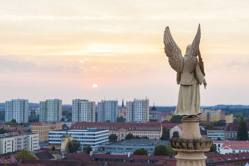 Germany, Potsdam, angel figurine of St. Nicholas church and concrete tower blocks in the background - WDF03787
