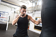 Boxer exercising at punch bag - MADF01229