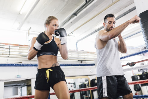 Female boxer practicing with coach - MADF01265