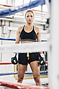 Portrait of confident female boxer in boxing ring - MADF01268