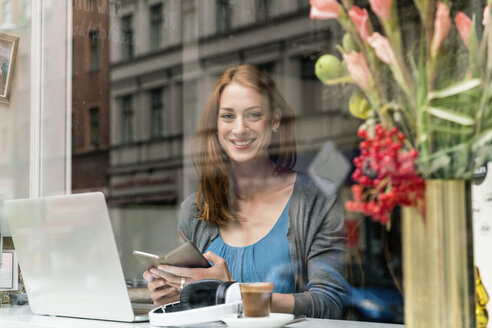 Portrait of smiling woman with smartphone and laptop in a coffee shop - TAMF00808