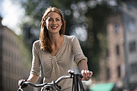 Portrait of redheaded woman with bicycle - TAMF00823