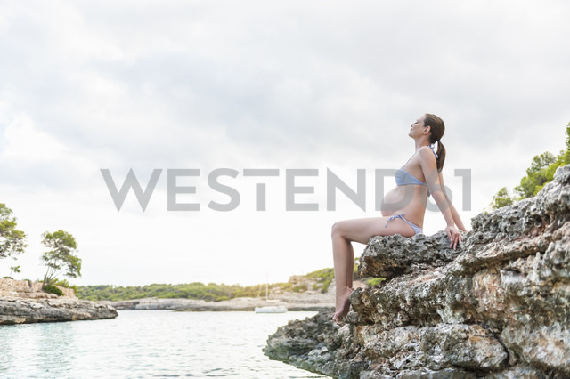Pregnant woman sitting on rock at the sea - DIGF01424 - Daniel Ingold/Westend61