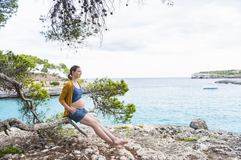 Pregnant woman sitting on branch at the sea - DIGF01439