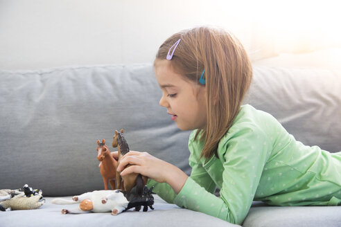 Little girl lying on couch playing with animal figurines - LVF05592