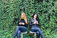 Two young women sitting side by side using their cell phones - GEMF01237