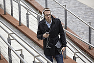 Young man with headphones and cell phone outdoors - FMKF03232