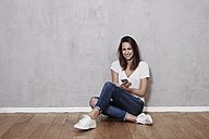 Smiling young woman sitting on the floor with cell phone - FMKF03241