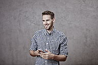 Smiling young man holding cell phone - FMKF03244