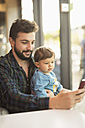 Father and son in a coffee shop looking together at cell phone - JASF01298