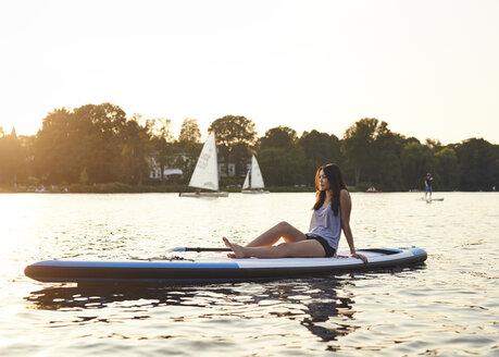 Germany, Hamburg, Young woman on paddleboard enjoying summer - WHF00039