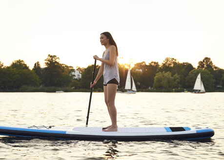 Germany, Hamburg, Young woman on paddleboard enjoying summer - WHF00042