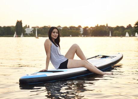 Germany, Hamburg, Young woman on paddleboard enjoying summer - WHF00048