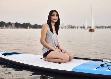 Germany, Hamburg, Young woman on paddleboard enjoying summer - WHF00051