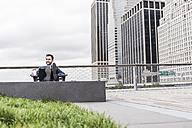 USA, New York, Manager in Manhattan sitting outdoor, using laptop - UUF09199