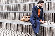 USA, New York City, Businessman sitting on stairs using digital tablet - UUF09226