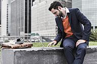 USA, New York City, Businessman working outdoor sitting on bench - UUF09229