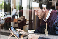 USA, New York City, Businessman sitting in coffee shop, using digital tablet - UUF09232
