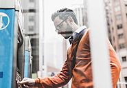 USA, New York City, Businessman using ATM - UUF09238