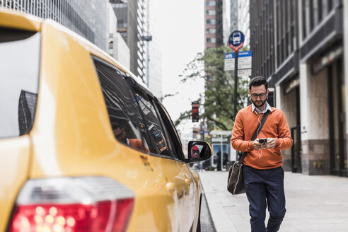 USA, New York City, Businessman approaching cab, using smart phone - UUF09244