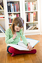 Little girl sitting on the floor reading a book - LVF05602