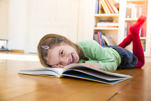 Laughing little girl lying on the floor with a book - LVF05605