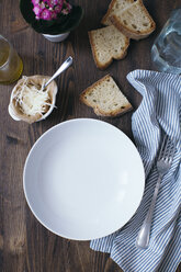Empty plate, parmesan, slices of white bread, cloth and fork on dark wood - DAIF00006