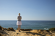 Woman standing at coast, looking at distance - CHPF00333