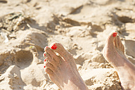 Feet with red nail varnish in sand - CHPF00336