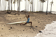Indonesia, Bali, woman with surfboard stretching on the beach - KNTF00577