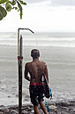 Indonesia, Bali, surfer taking a shower in rain - KNTF00583