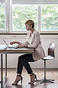 Businesswoman using laptop in modern conference room - RIBF00588