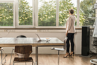 Businesswoman standing at the window in modern conference room - RIBF00591