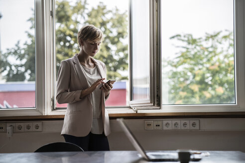 Businesswoman using cell phone in office - RIBF00594