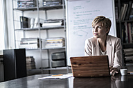 Businesswoman with laptop in modern conference room - RIBF00597