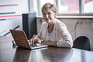 Portrait of smiling businesswoman with laptop in modern conference room - RIBF00606