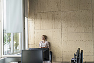 Smiling businesswoman with cell phone in office - RIBF00609