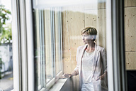 Businesswoman looking out of window - RIBF00612