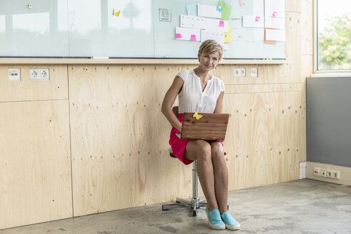 Smiling businesswoman using laptop at wooden wall with board - RIBF00624