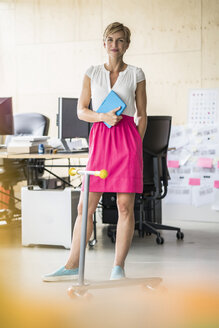 Woman standing in creative office - RIBF00630