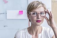Portrait of businesswoman in front of whiteboard in modern office - RIBF00645
