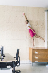 Businesswoman putting sticky note on wooden wall - RIBF00648